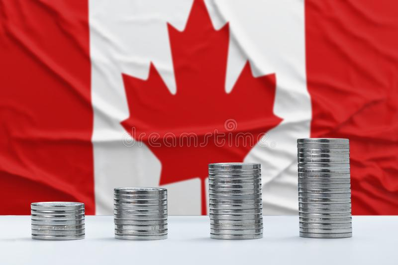 Wrinkled Canada flag in the background with rows of coins for finance and business concept. Saving money stock photography