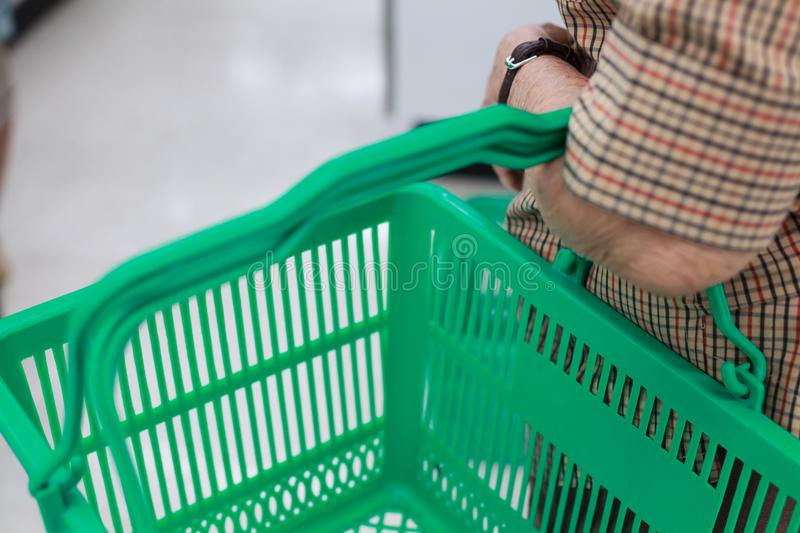 Wrinkled elderly woman`s hand holding shopping basket in shopping mall. Health care, Help, Support, Lifestyle, Senior Workforce, royalty free stock photo