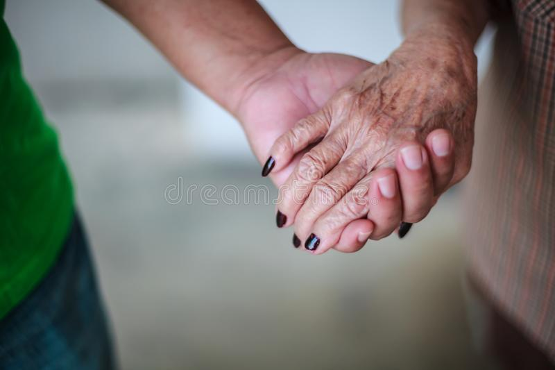 Wrinkled elderly woman`s hand holding to young man`s hand, walking in shopping mall park. Family Relation, Health, Help, Support royalty free stock images