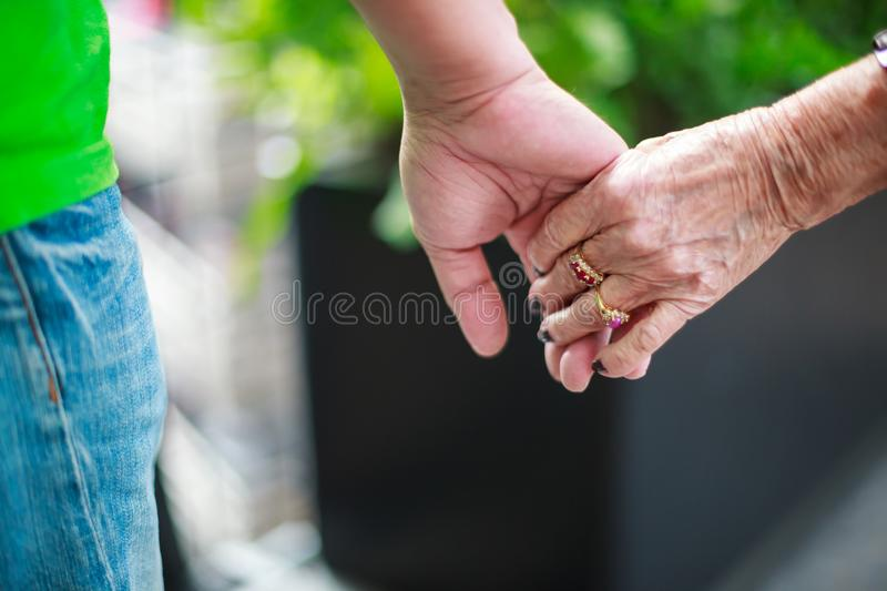 Wrinkled elderly woman`s hand holding to young man`s hand, walking in shopping mall park. Family Relation, Health, Help, Support, stock photography