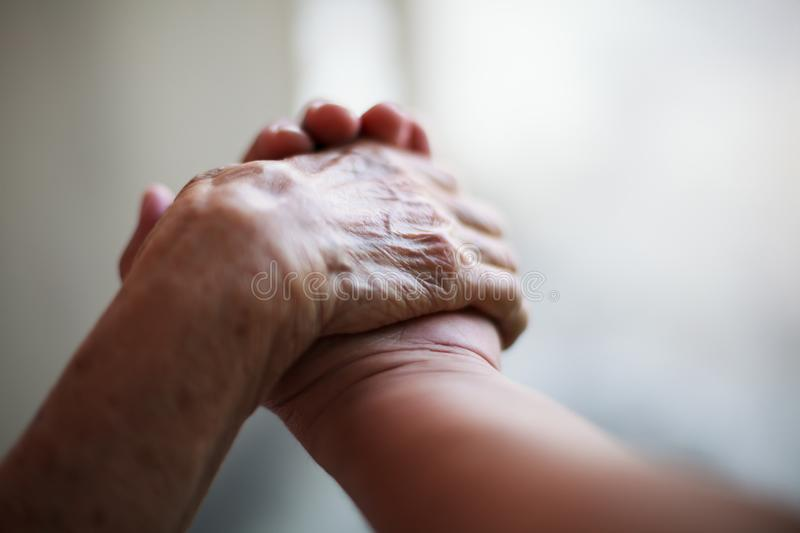 Wrinkled elderly woman`s hand holding to young man`s hand, walking in shopping mall park. Family Relation, Health, Help, Support stock image