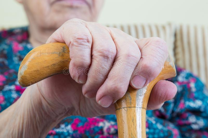 Wrinkled hand of a senior woman on cane royalty free stock photography