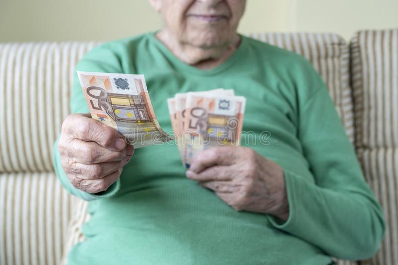 Wrinkled hand of a senior woman holding euro banknotes stock photos