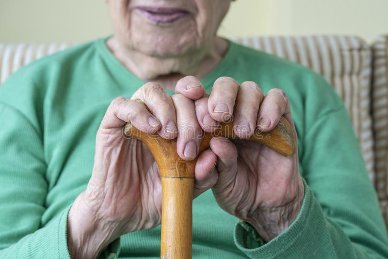 Wrinkled hands of a senior person holding a walking cane royalty free stock photos