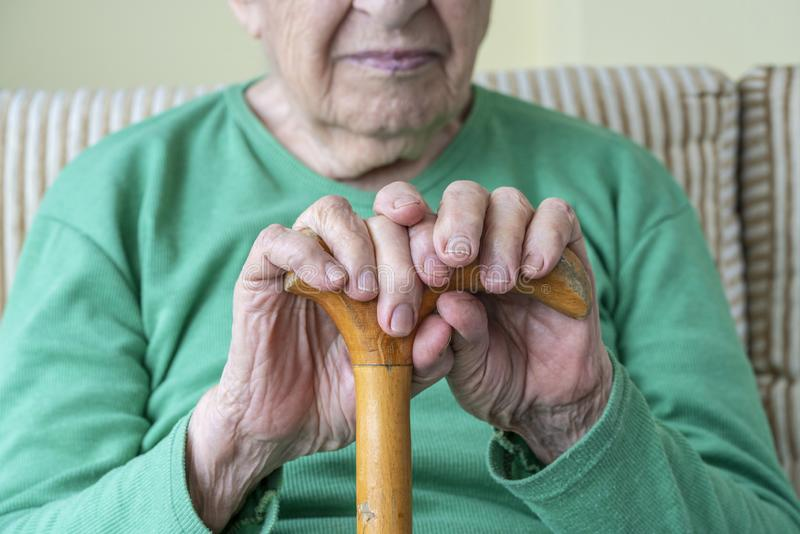 Wrinkled hands of a senior person holding a walking cane stock images