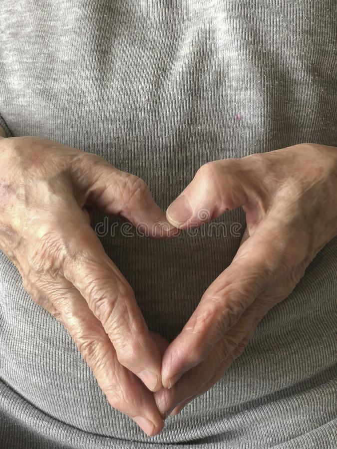Wrinkled hands of a senior person, making heart shape royalty free stock image