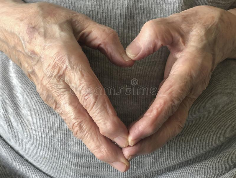 Wrinkled hands of a senior person, making heart shape stock images