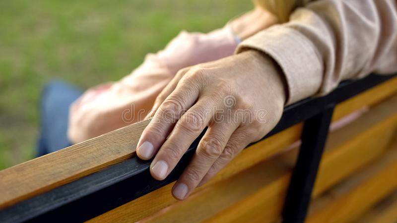 Wrinkled male hand hugging woman during outside date, spouse care, attention royalty free stock photography