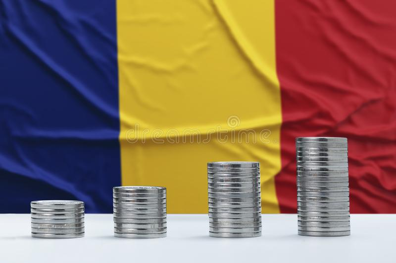 Wrinkled Romania flag in the background with rows of coins for finance and business concept. Saving money stock image