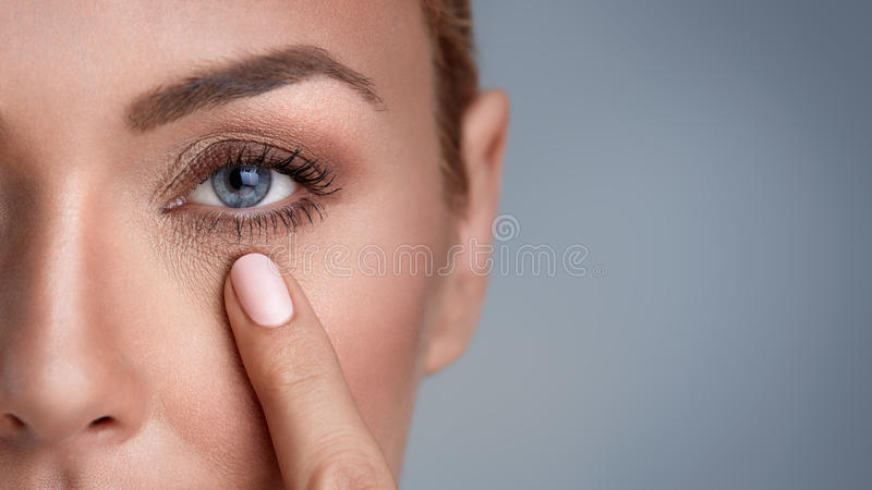 Wrinkles around the eyes. Woman checking wrinkles around the eyes, close up royalty free stock image