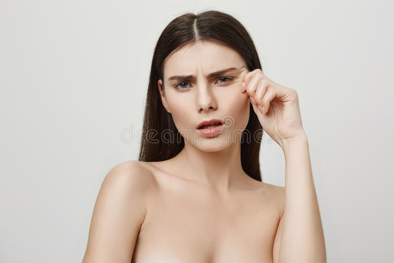 Wrinkles attacking her beautiful face. Studio shot of upset irritated young european woman, standing naked while pulling royalty free stock photo