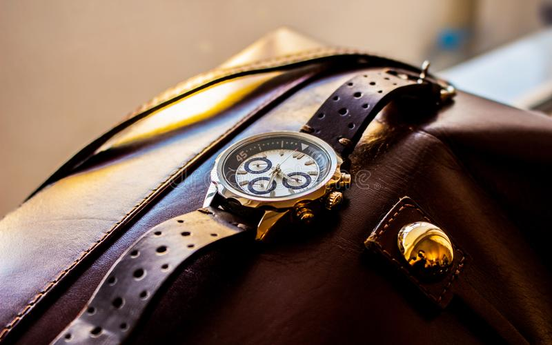 Wrist man watch showing time. Product photography of a man wrist watch showing time on leather material background royalty free stock photos