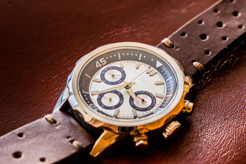 Wrist man watch showing time. Product photography of a man wrist watch showing time on leather material background royalty free stock photography
