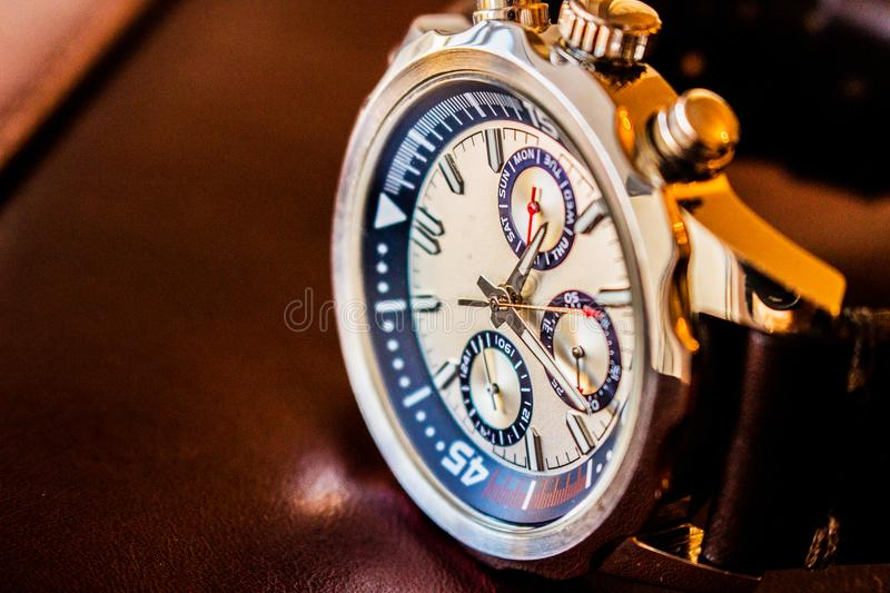 Wrist man watch showing time. Product photography of a man wrist watch showing time on leather material background stock images
