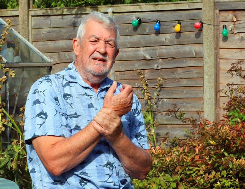 Wrist pain. Arthritis. Senior in pain. Elderly or senior man holding his wrist because of pains. Arthritis in his joints stock photos