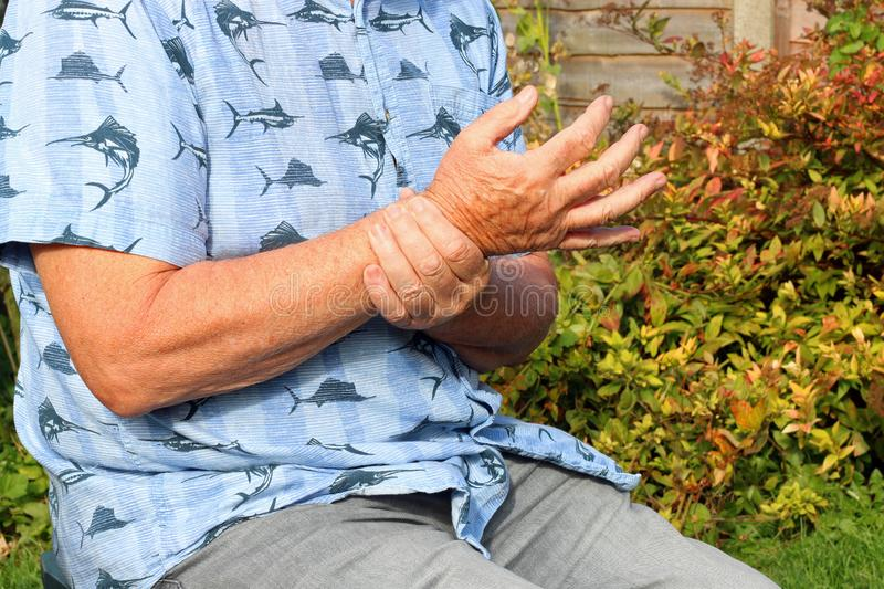 Wrist pain. Arthritis. Senior in pain. Elderly or senior man holding his wrist because of pains. Arthritis in his joints stock photography