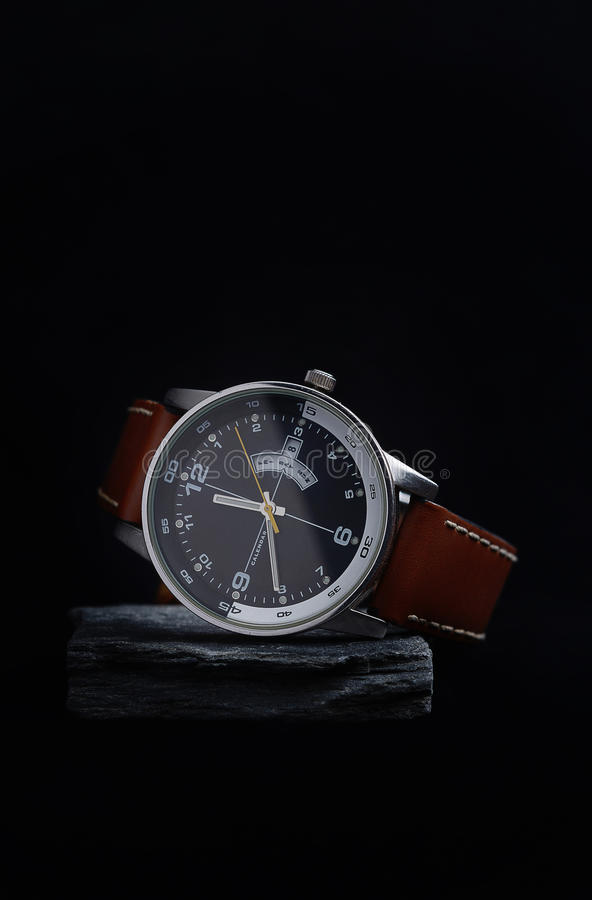 Wrist watch with a black dial on a gray stone. stock photos