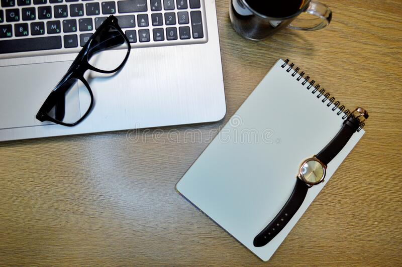 Wrist Watch, laptop, notebook, coffee and glasses on wooden background. Mix of office supplies and gadgets on a wooden table background. View from above. Wrist stock image