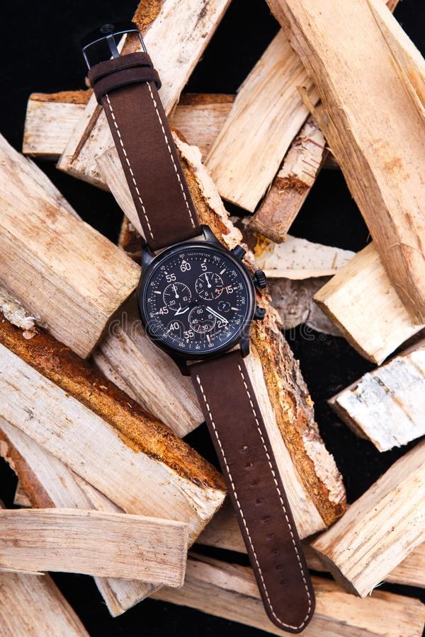 Wrist watch men`s brown leather strap on wood. royalty free stock image