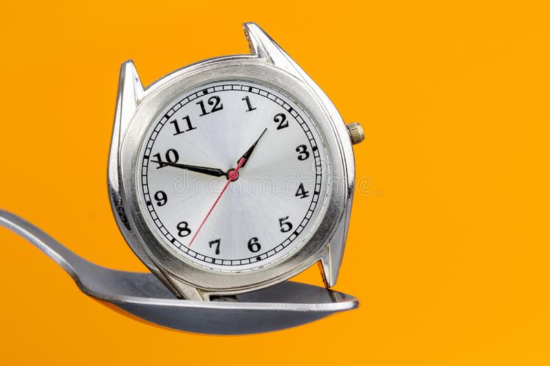 Wrist watch without strap with arrows located in a metal spoon on an orange background stock image