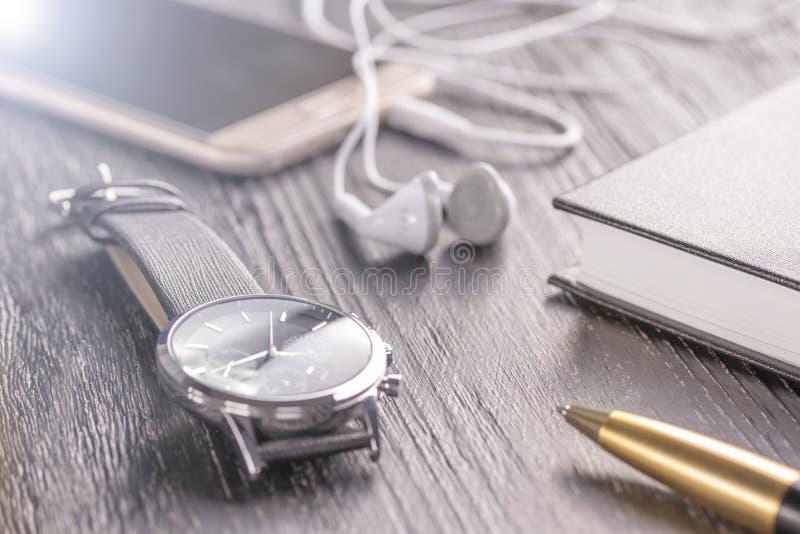 Wristwatch, κινητό τηλέφωνο με τα ακουστικά και ένα σημειωματάριο με μια μάνδρα σε έναν παλαιό σκοτεινό υπολογιστή γραφείου γραφε στοκ φωτογραφία με δικαίωμα ελεύθερης χρήσης