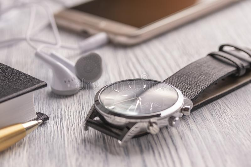 Wristwatch, κινητό τηλέφωνο με τα ακουστικά και ένα σημειωματάριο με μια μάνδρα σε έναν παλαιούς άσπρους υπολογιστή γραφείου και  στοκ εικόνα με δικαίωμα ελεύθερης χρήσης