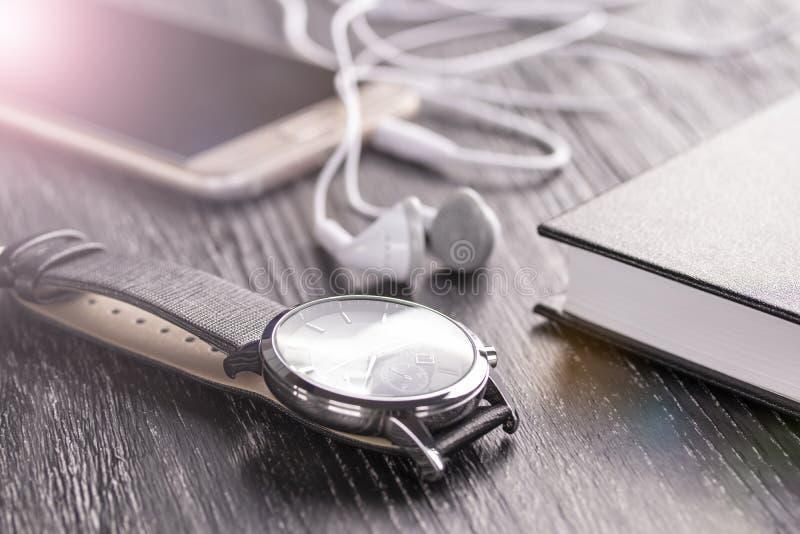 Wristwatch, κινητό τηλέφωνο με τα ακουστικά και σημειωματάριο σε έναν παλαιό σκοτεινό υπολογιστή γραφείου γραφείων στοκ φωτογραφία με δικαίωμα ελεύθερης χρήσης
