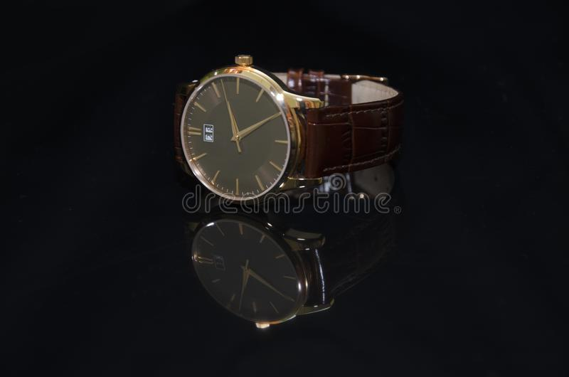 Wristwatch in gold on a black background stock images