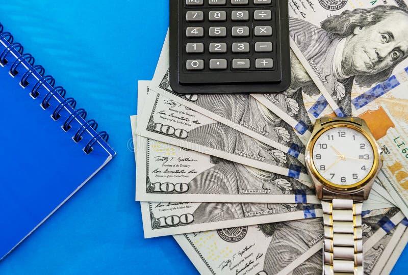Wristwatch na dolarach i kalkulatorze zdjęcia stock