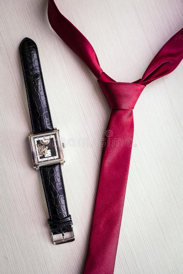 Wristwatches and red tie of the groom stock photo