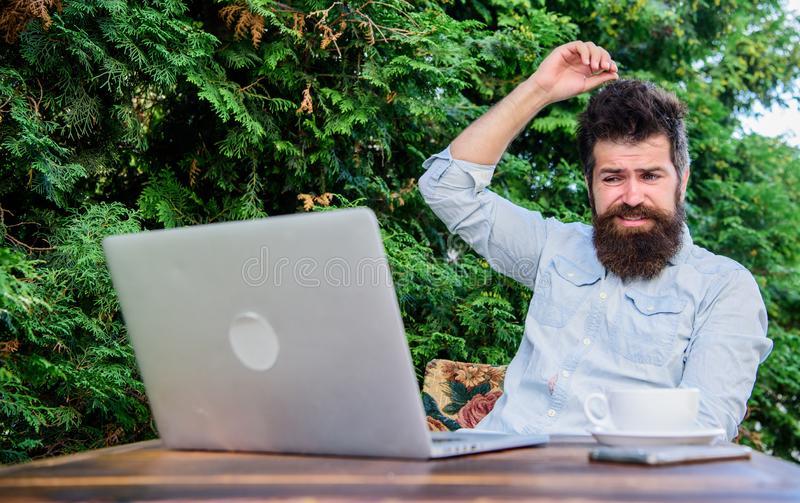 Write article for online magazine. Bearded hipster laptop surfing internet. Man looking for inspiration. Reporter royalty free stock image