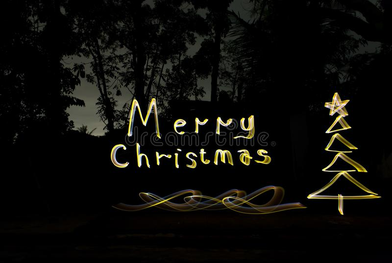Write christmas greetings with golden lights at night royalty free stock photo