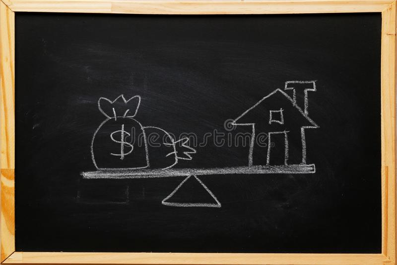 Write dollar bags and house symbol on basic balance scale on blackboard with chalk. family finance and child trust fund concept. Cost of living, home loan stock photography