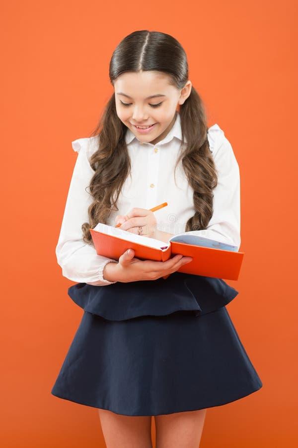 Write essay or notes. Inspiration for study. Back to school. Knowledge day. Schoolgirl enjoy study. Kid school uniform. Hold workbook. School lesson. Child stock image
