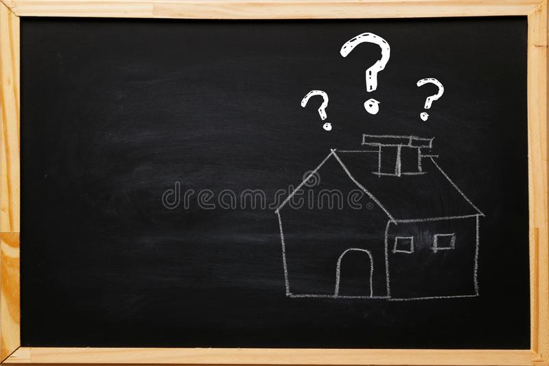 Write house symbol with question marks on blackboard with chalk.  stock photography