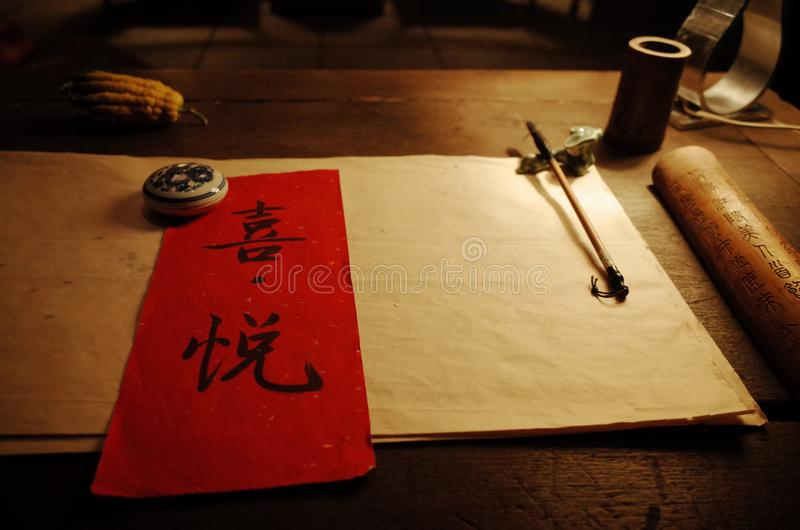 Write `joy` in Chinese calligraphy on the paper. This is in the study of a Chinese restaurateur royalty free stock image