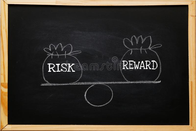 Write symbol Risk and reward bags on a basic balance scale in equal position on blackboard. risk management concept, depicts. Investors use a risk reward ratio stock images