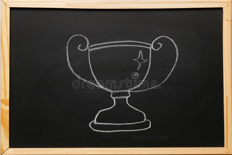 Write trophy symbol on blackboard with chalk. Trophy is a tangible, durable reminder of a specific achievement excellence in. Activities royalty free stock image