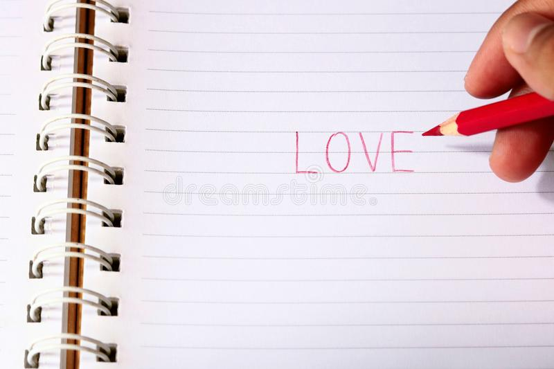 Write the word love with red pencil in blur man`s hands stock image