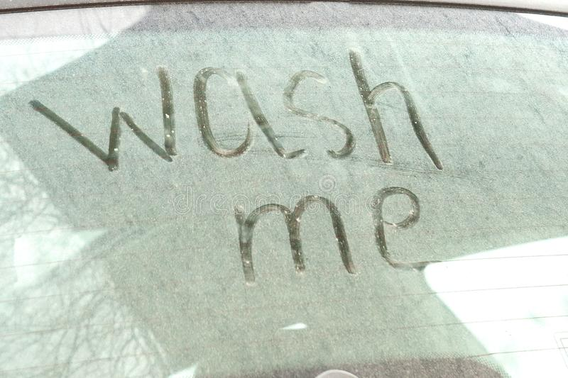 Write the words wash me on the very dirty surface of the car. Concept car wash royalty free stock photos