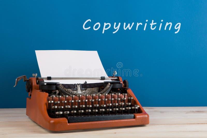 """writer';s工作场所-在蓝色黑板背景的打字机与文本"""";Copywriting 免版税库存照片"""