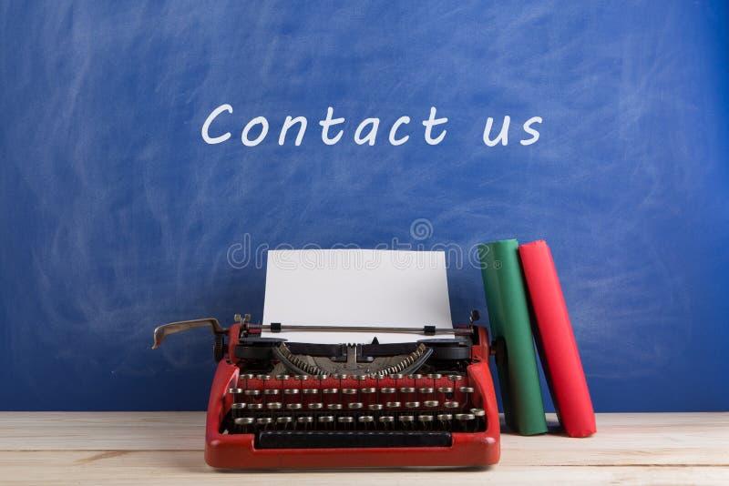 """writer';s工作场所-打字机和书在蓝色黑板背景与文本"""";与我们联系 免版税图库摄影"""