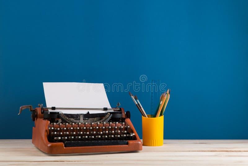 writer';s工作场所-红色打字机和文具在蓝色黑板背景 免版税库存照片