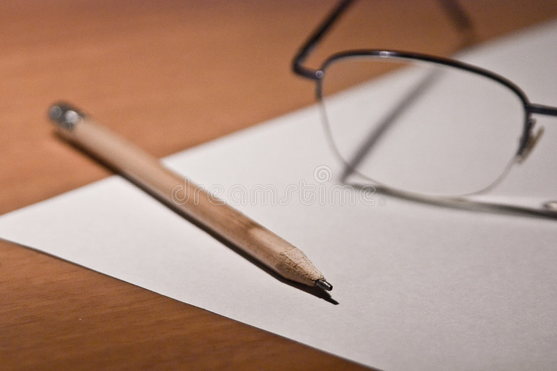 Writer. A writer let his glasses and his pencil thinking about how to start his composition royalty free stock photography