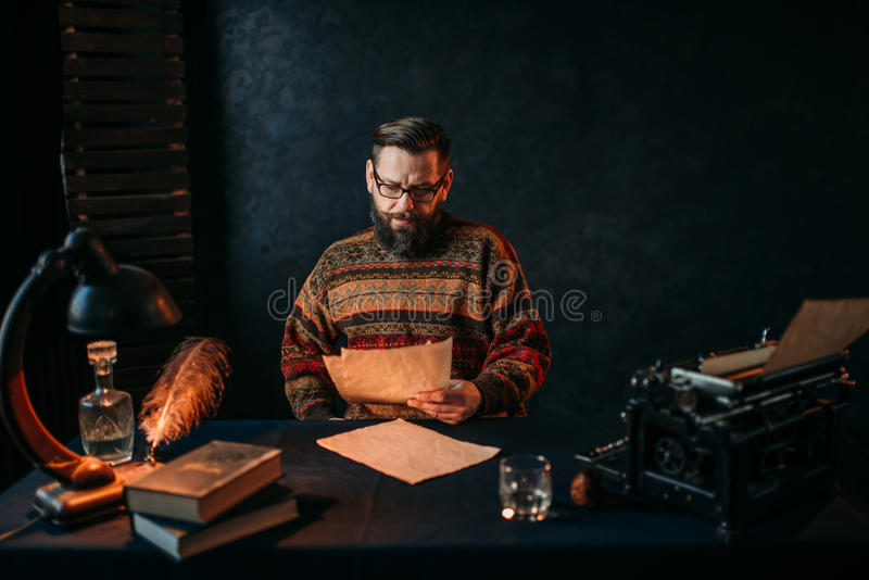 Writer in glasses reading his literature text. Thoughtful bearded writer in glasses reading his literature text. Retro typewriter, feather, crystal decanter royalty free stock images