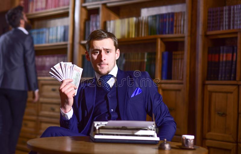 Writer got honorarium for new book. Writer or author. With strict face with typewriter in library with books on background, defocused. Writing and fees concept stock photo