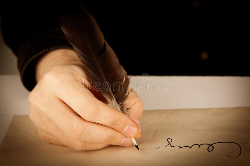 Writer holds a fountain pen over writing paper and a signature stock images