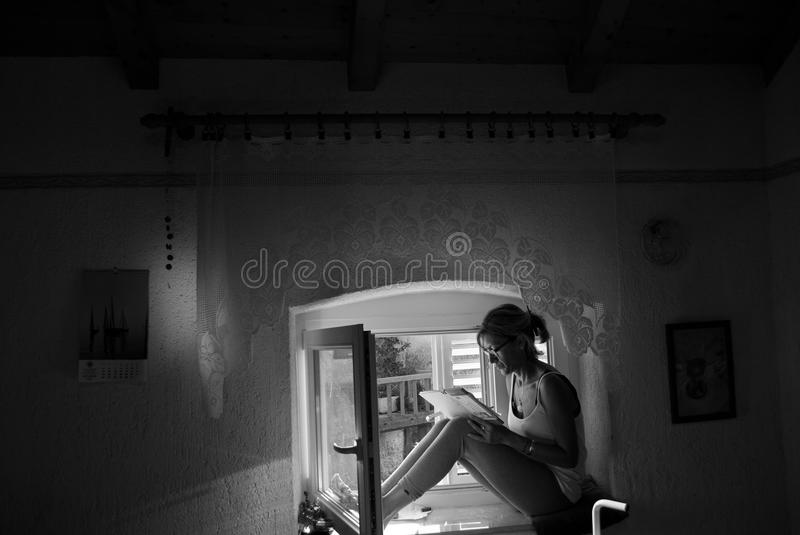 The writer re-reading her notes sitting on the window. The woman writing and reading in a small attic in Croatia, on summer days, resting