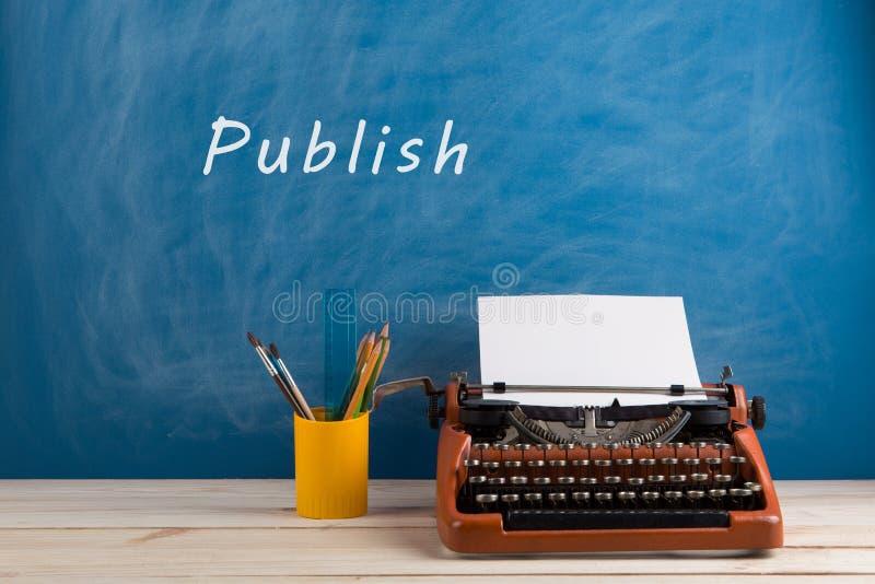writer' s-arbetsplats - skrivmaskin och brevpapper på blå svart tavlabakgrund med text ' Publicera royaltyfria foton