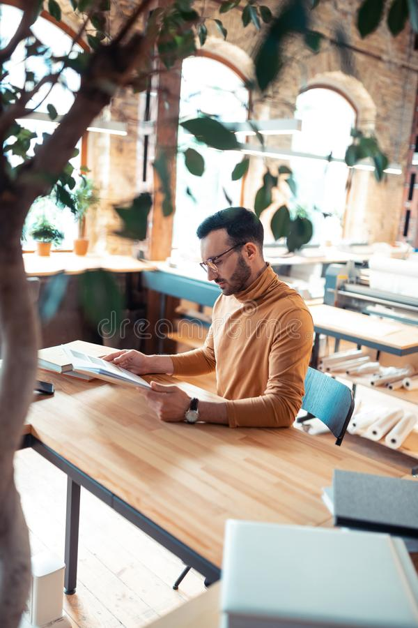Writer wearing orange polo neck sitting at the wooden table royalty free stock photos